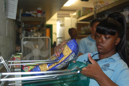 Police Ambassador Shaquirra Johnson bags pasta in the church's food pantry. (Photo by Devi Shastri)