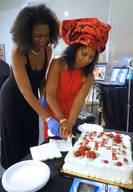 Dawn Sanders (left), daughter of the late Welford Sanders, and Marquita Edwards, artistic director of the King Drive Commons Gallery and Studio, cut a piece of cake during a celebration of the late developer's contributions to the community. (Photo by Adam Carr)