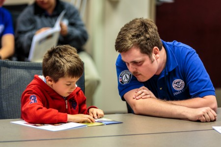 A FEMA Corps member talks with a young child about emergency preparedness. (Photo courtesy of FEMA/Steve Zumwalt)