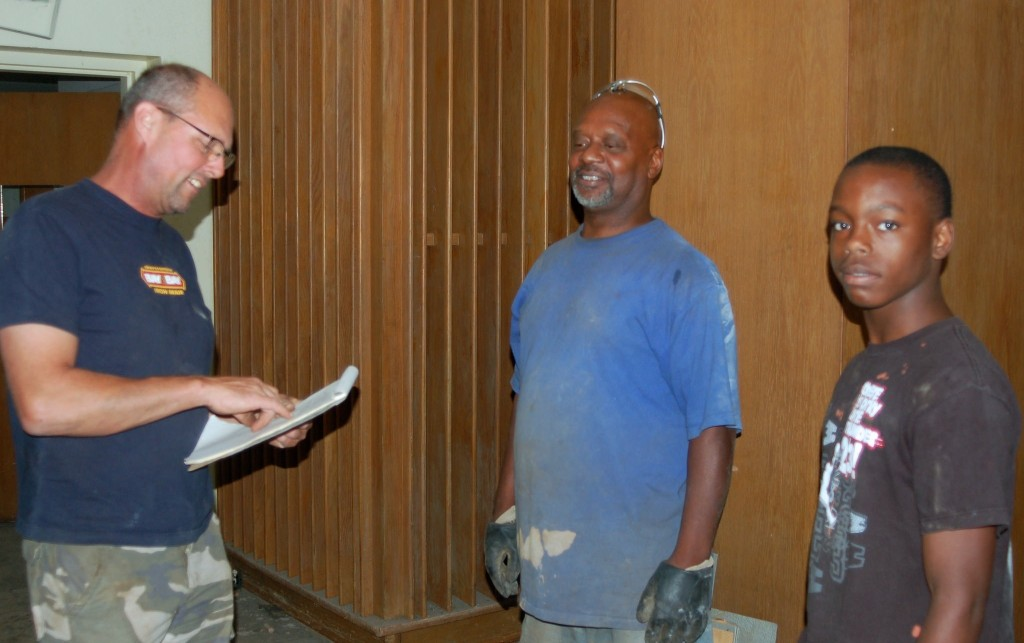Matt Bohlmann (right), the new owner of the former Finney Library building, consults with Ken Maclin (left) and Dontrell Jackson about demolition work they are doing at the site. (Photo by Andrea Waxman)