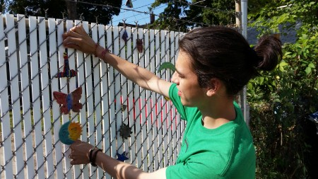 Clarke Square artist Lucas Alamo hangs a ceramic medallion on the fence. (Photo by Edgar Mendez)