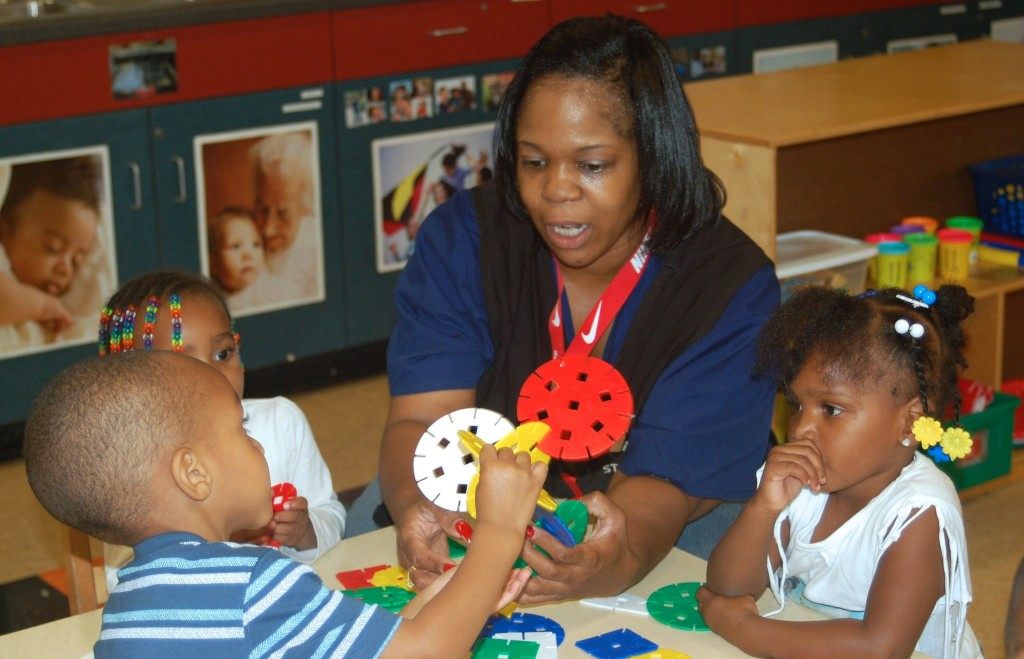 Nikole Foster, an early childhood education teacher, helps students with an art project at the Northside YMCA location. (Photo by Stephanie Harte)