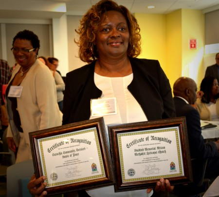 Gerri Sheets-Howard of Capuchin Community Services shows off plaques of appreciation she received for supporting expectant mothers in Milwaukee. (Photo by Marlita A. Bevenue).