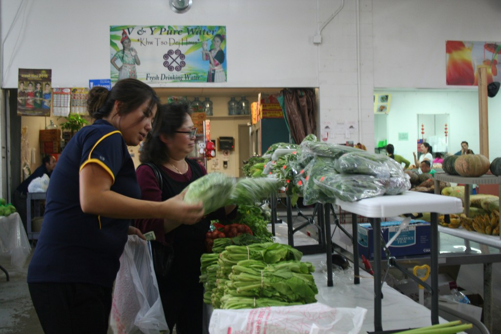 Mailee Yang, who is the daughter of the Phongsavan Market's owner Pai Yang, helps a customer pick out fresh vegetables. (Photo by Jabril Faraj)