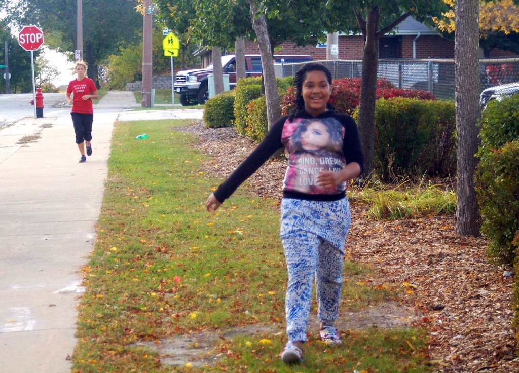 A participant in Kids Run Milwaukee rejoices as she finishes her last lap of the day. (Photo by Allison Dikanovic)