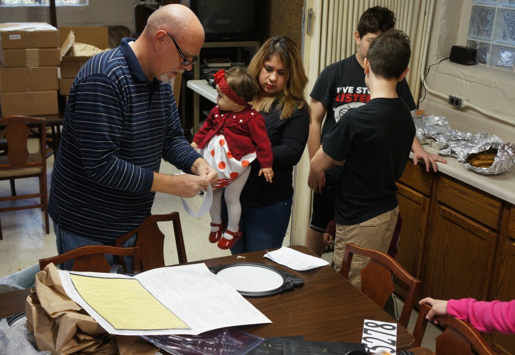 Pastor Jim Anderson helps Maribel Hernandez assemble her address plaque while she holds her baby, Elizabeth. (Photo by Adam Carr)
