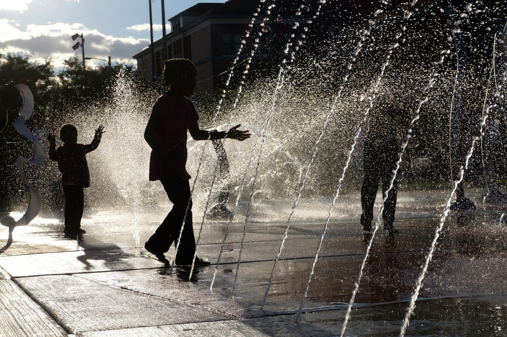 Neighborhood youth play in the splash pad after opening ceremonies for the renovated Moody Park. (Photo by Adam Carr)
