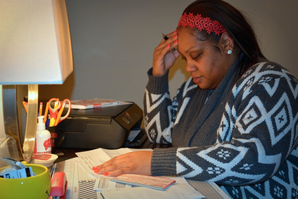 Latoya S. sits at her desk looking through overdue bills. Since 1998, she's taken out close to 20 short-term payday loans. (Photo by Marlita A. Bevenue)