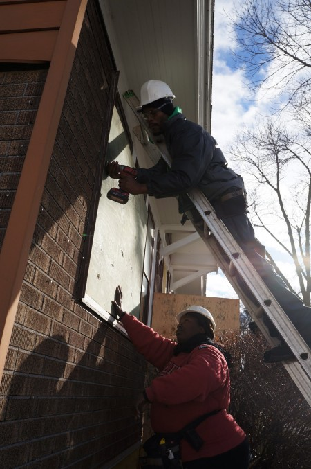 Workers put boards up to protect windows at a house being renovated by the Northside Housing Initiative. (Photo by Adam Carr)