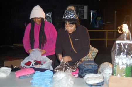 Valencia Halloway (right) and her daughter Lamiya Tuggles fold clothes for a rummage sale during a recent Club Kids 414 cleanup event and fundraiser. (Photo by Edgar Mendez)