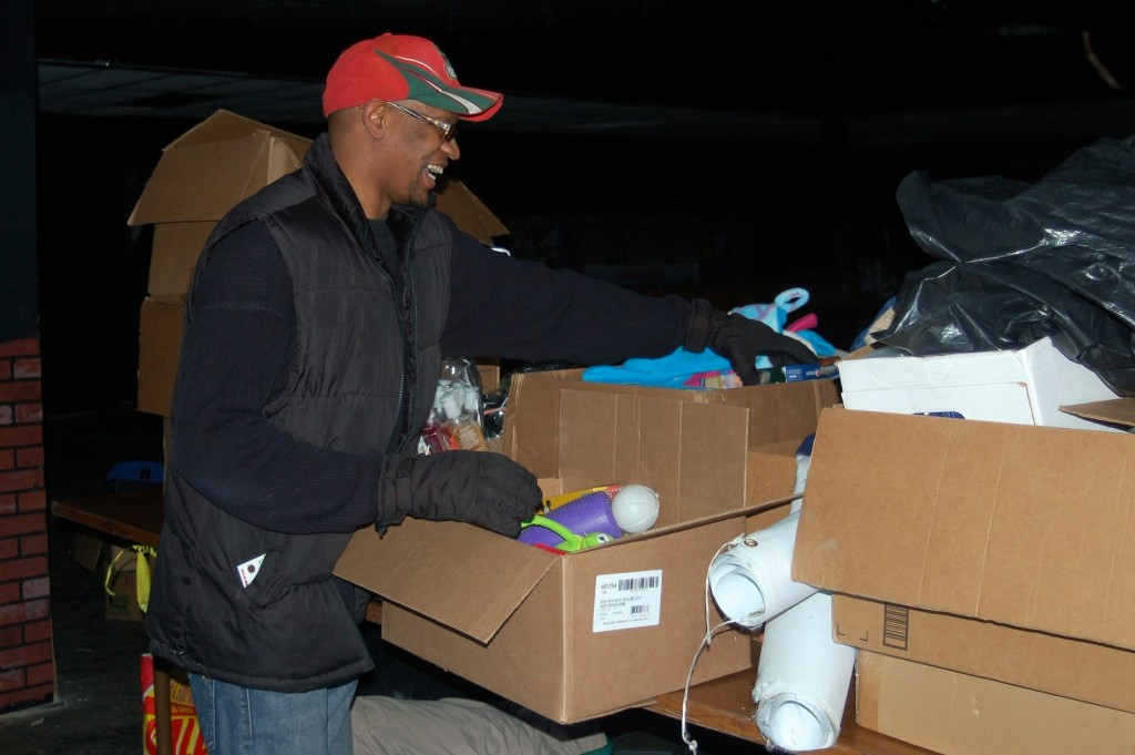 Marcus Duke, executive director of Club Kids 414, organizes donated materials at the North Avenue building. (Photo by Edgar Mendez)