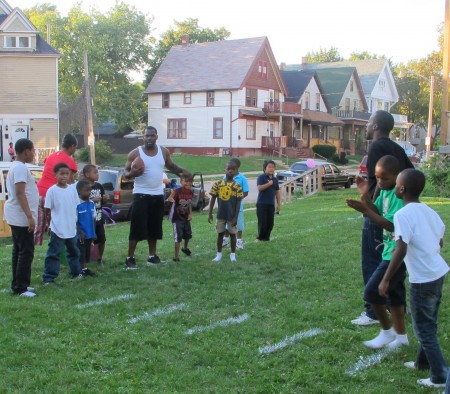 Field manager Markevin Brown holds the football at the 2012 opening of Fox Field, a vacant lot transformed by Safe & Sound and residents of the 2000 block of North 41st Street. (Photo by Andrea Waxman)