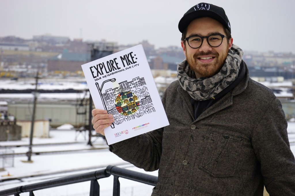 "Author Adam Carr displays his new book, ""Explore MKE,"" with Menomonee Valley in the background. (Photo by Brendan O'Brien)"