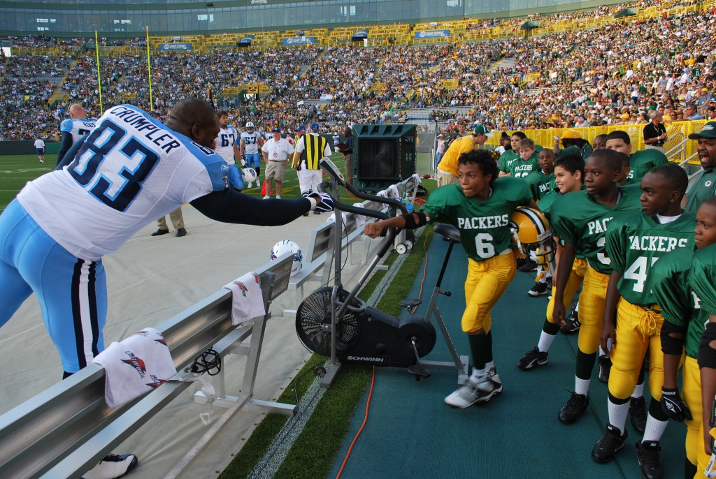 Anthony Barron, former quarterback of the Journey House Packers football team, (right) bumps fists with NFL football player Alge Crumpler (left) at Lambeau Field. (Courtesy of Charles Brown.)