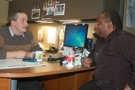 Bill Mullooly speaks with community health worker Johnny Ayers at the St. Ben's Clinic for the Homeless. (Photo by Devi Shastri)