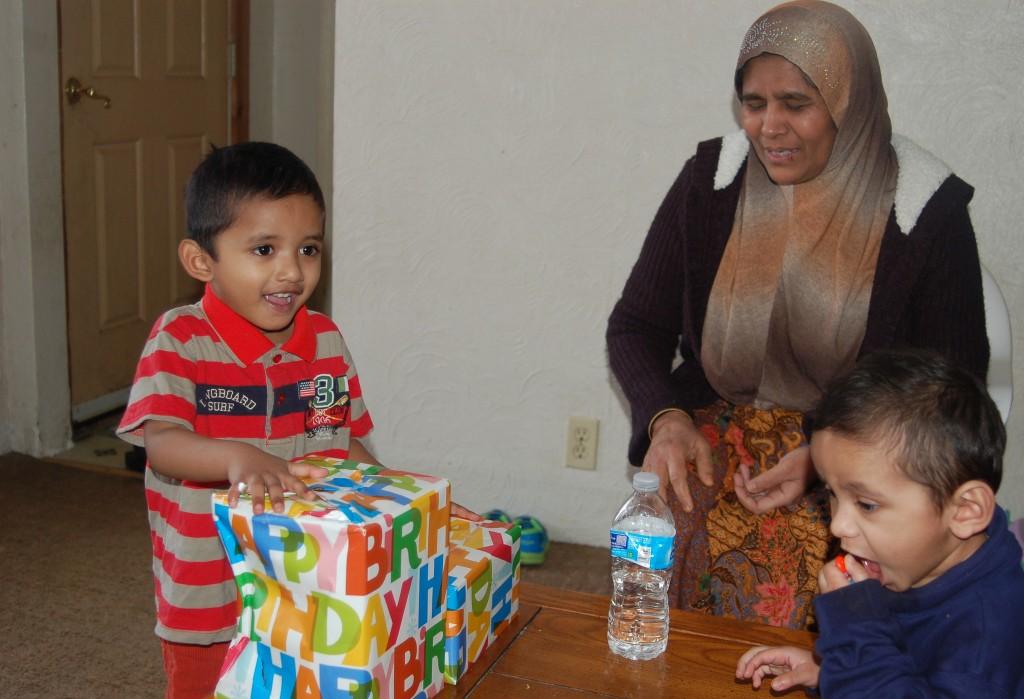 Sufaidul Sirajul Kadir, 3, opens a birthday present from International Institute volunteer Cindy Angelos as his grandmother, Saliya Begum binti Jalal Ahmad, and younger brother, Hubaib Sirajul Kadir, 2, look on. (Photo by Andrea Waxman)