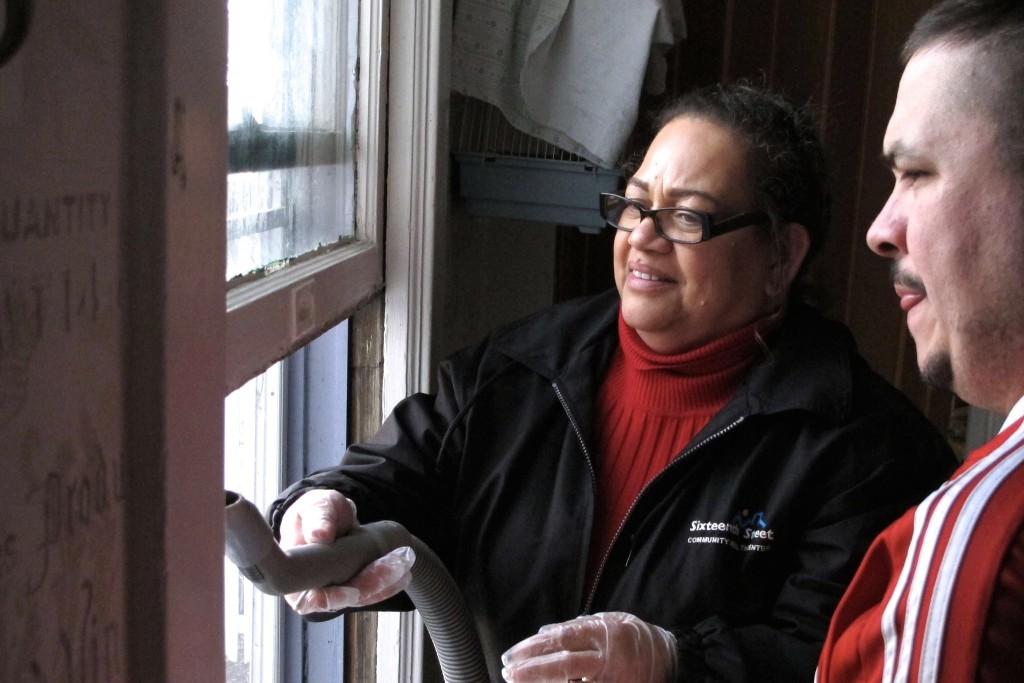 Carmen Reinmund (left) vacuums chipped lead paint from a windowsill as South Side homeowner Armando Martinez watches. (Photo by Wyatt Massey)