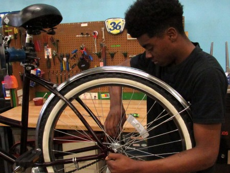 Devin Burton, 18, has been working at DreamBikes as a bicycle mechanic for the past two years. (Photo by Morgan Hughes)