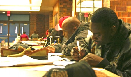 Deshawn Nabors (foreground) and other attendees fill out applications. (Photo by Jabril Faraj)