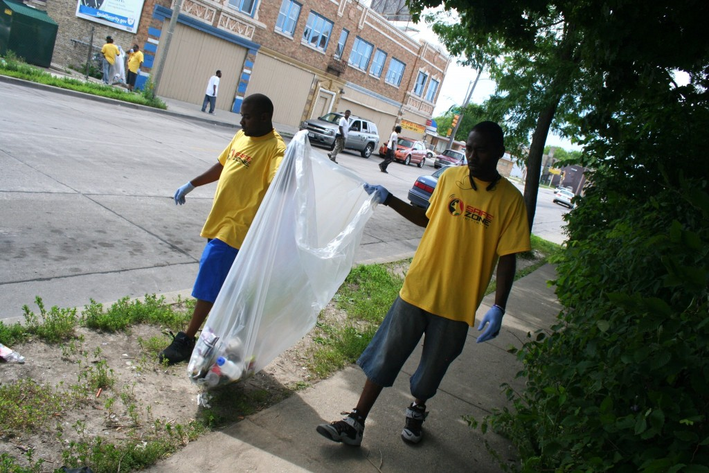 Safe Zones co-founder Khalil Coleman (left) and ambassador Teddy Ellis pick up garbage on W. Atkinson Avenue in Garden Homes. (Photo by Jabril Faraj)