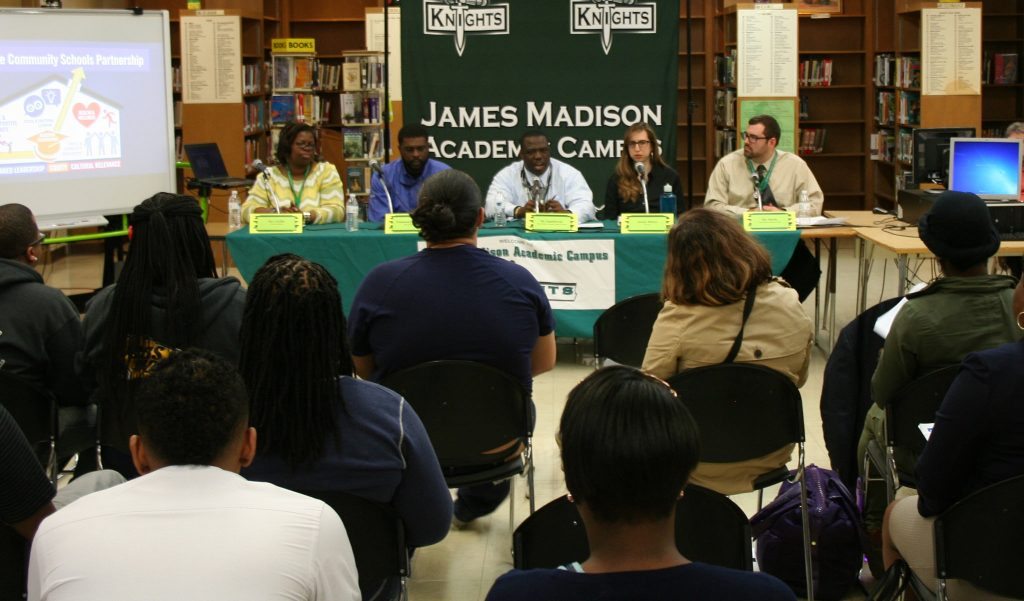 James Madison Principal Gregory Ogunbowale (center) speaks to community members and parents during a recent event focused on community schools. (Photo by Jabril Faraj)