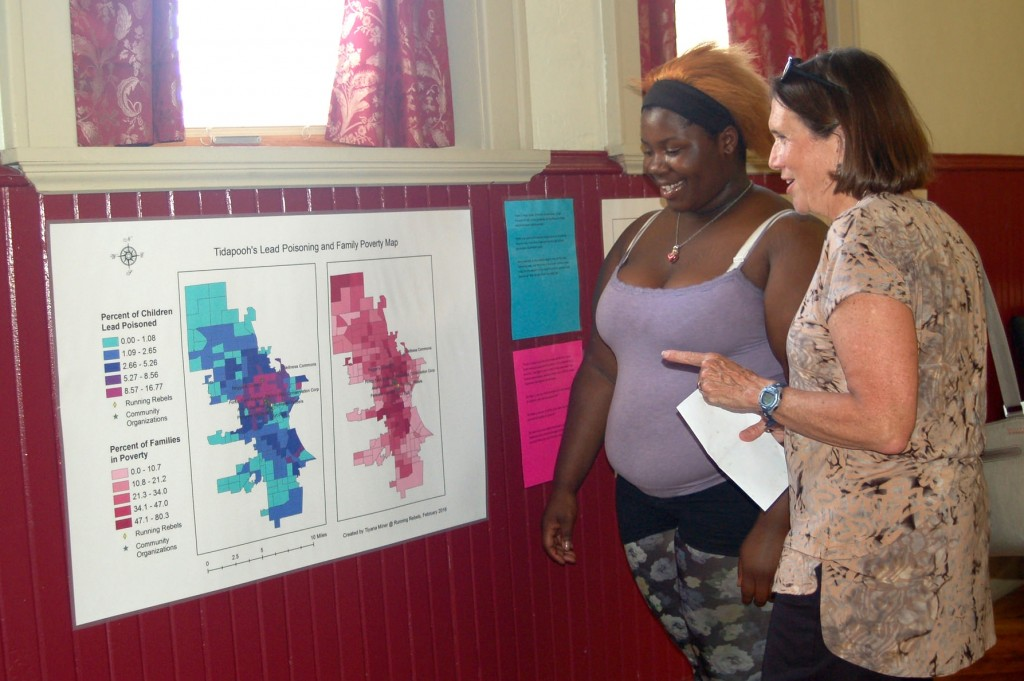 Tiyana Miner, a member of the Running Rebels Youth Advisory Council, shows a guest the series of maps council members created. (Photo by Rebecca Carballo)