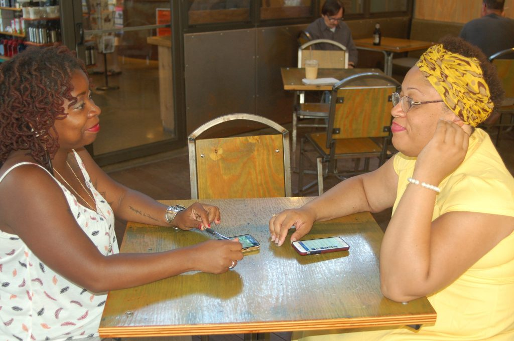 Symphony Swan (left) and Bridget Robinson, co-founders of BlankSpaceMKE, discuss final details of Milwaukee Black Arts Week at a local coffee shop. (Photo by Andrea Waxman)