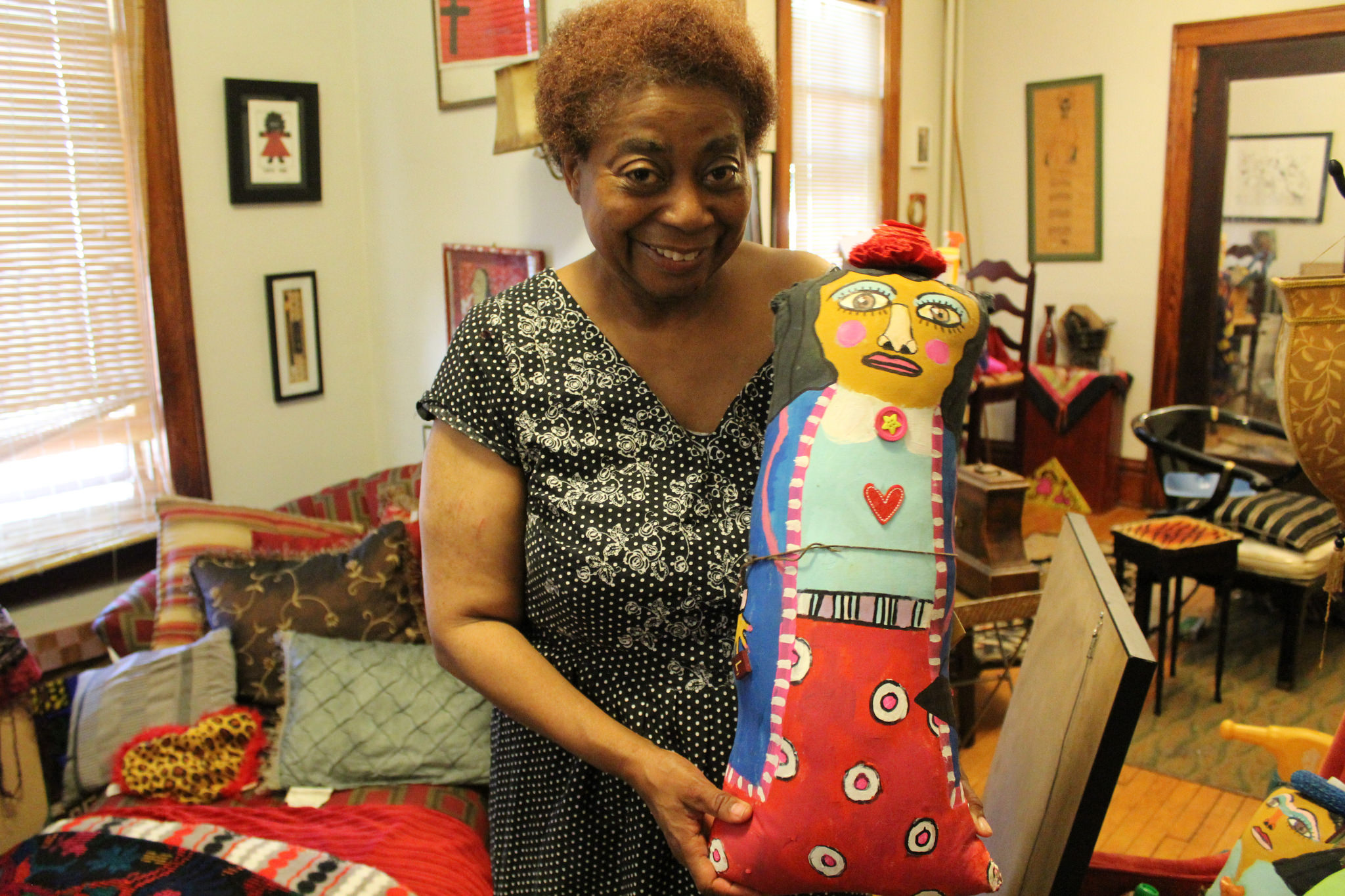 Artist Della Wells displays one of her handmade dolls in her home. (Photo by Emmy A. Yates)