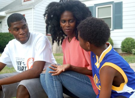 Brothers Isaiah Thornton, 18 (left) and J'Ali Thorton, 9, talk with their mother, Latrina Thornton, on their front walk. (Photo by Andrea Waxman)