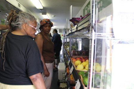 Shoppers browse through the produce section at the Fresh Picks Mobile Market, which carries vegetables, meat and other refrigerated items. (Photo by Rebecca Carballo)