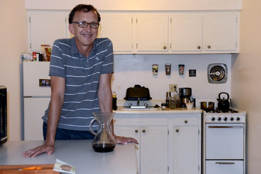Robert Itzin, who was once chronically homeless, stands in the kitchen of his apartment, provided by Housing First. (Photo by Sue Vliet)