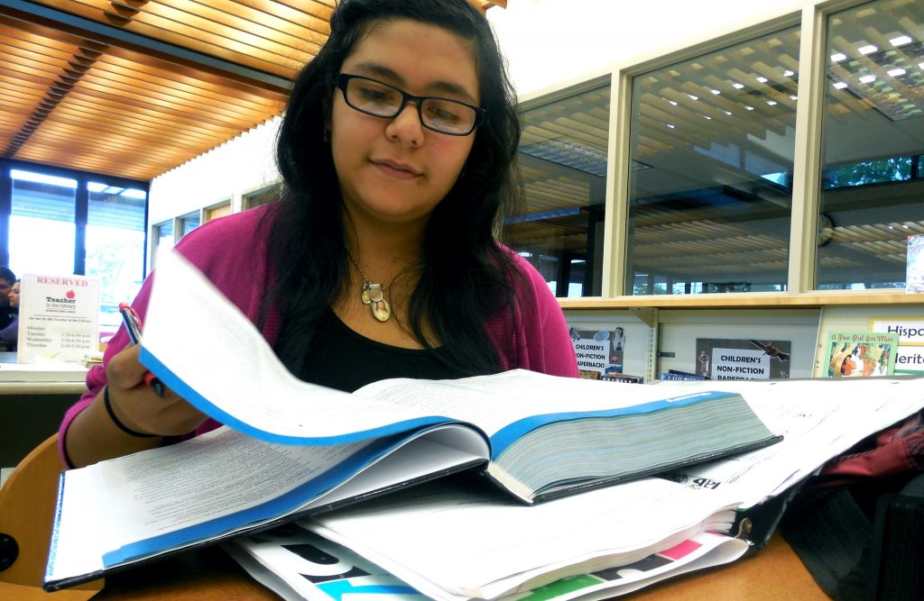 Yudith Arenas, 14, is a freshman at Ronald Reagan High School and does homework at Forest Home Library. (Photo by Maria Corpus)