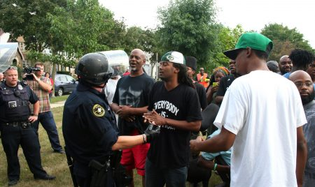 Frank Sensabaugh speaks with a police officer before a young man was taken into police custody without incident. (Photo by Jabril Faraj)