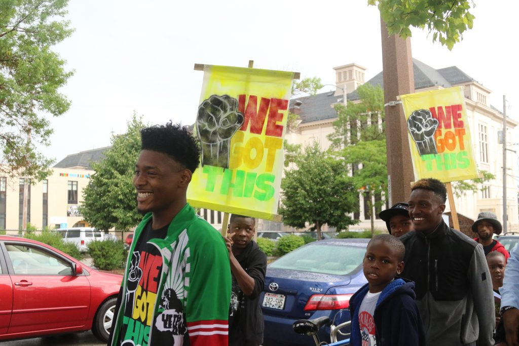 "Participants in ""We Got This"" march with handmade signs down Dr. Martin Luther King Drive during the 14th Annual Summer of Peace Rally. (Photo by Amelia Jones)"