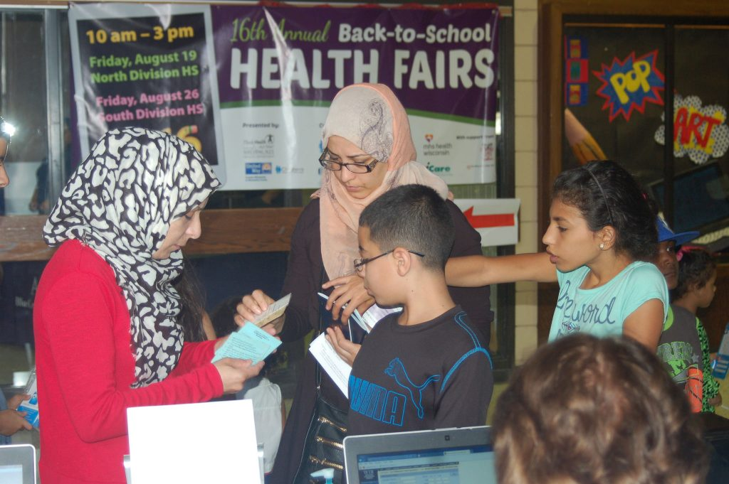 A family checks in at the South Division High School health fair. (Photo by Clara Hatcher)