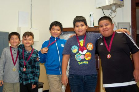 Students from the Escuela Vieau chess team pose for a photo with their medals from the chess tournament. (Photo by Brittany Carloni)
