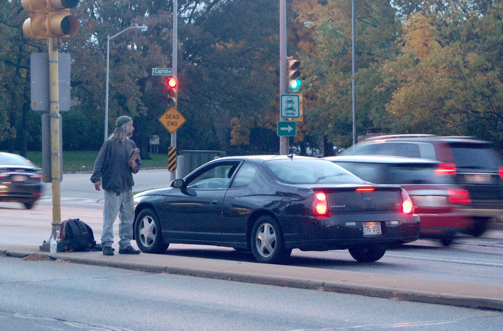 "A panhandler on a Capitol Drive median at Humboldt Avenue holds a sign that says ""Hungry."" (Photo by Andrea Waxman)"
