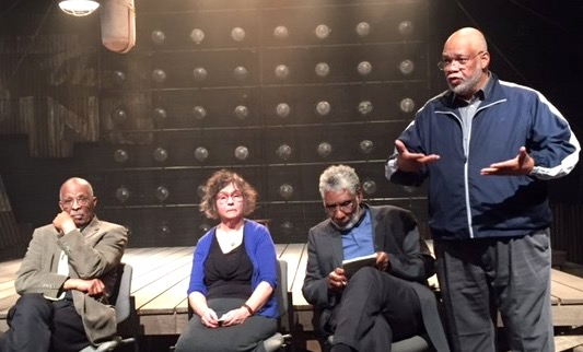 "Moderator Everett Marshburn (standing, right), executive producer of Milwaukee Public Television's Black Nouveau, introduces the panel after a performance of ""The Royale.""  The panelists are (from left) Prentice McKinney, Margaret Rozga and Fred Reed."