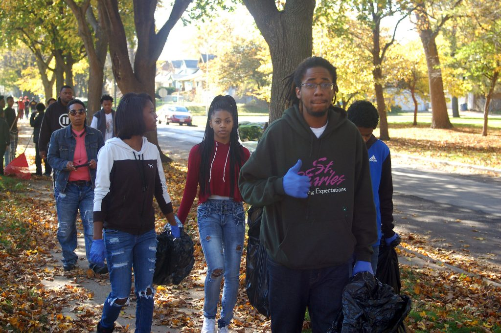 Teens walk back up 41st Street after raking lawns south of Sherman Park. (Photo by Andrea Waxman)