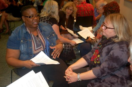 "Terri Ellzey (left) and Shelly Schnupp discuss the article ""11 Common Ways White Folks Avoid Taking Responsibility for Racism in the U.S."" at a YWCA Southeast Wisconsin ""talk back"" on racial justice. (Photo by Clara Hatcher)"