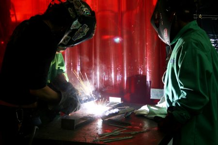 Jennifer Kessenich (left) demonstrates welding, as Bradley Tech freshman Zantrell Irvin looks on. (Photo by Jabril Faraj)