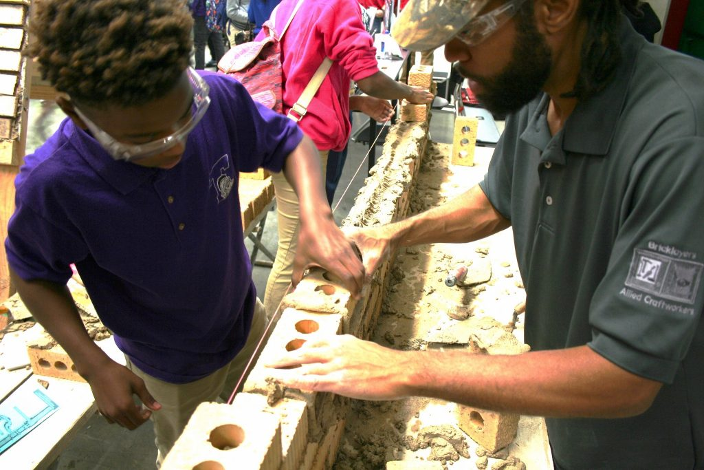 Tim Brown (right) helps a student lay a brick during the event. (Photo by Jabril Faraj)