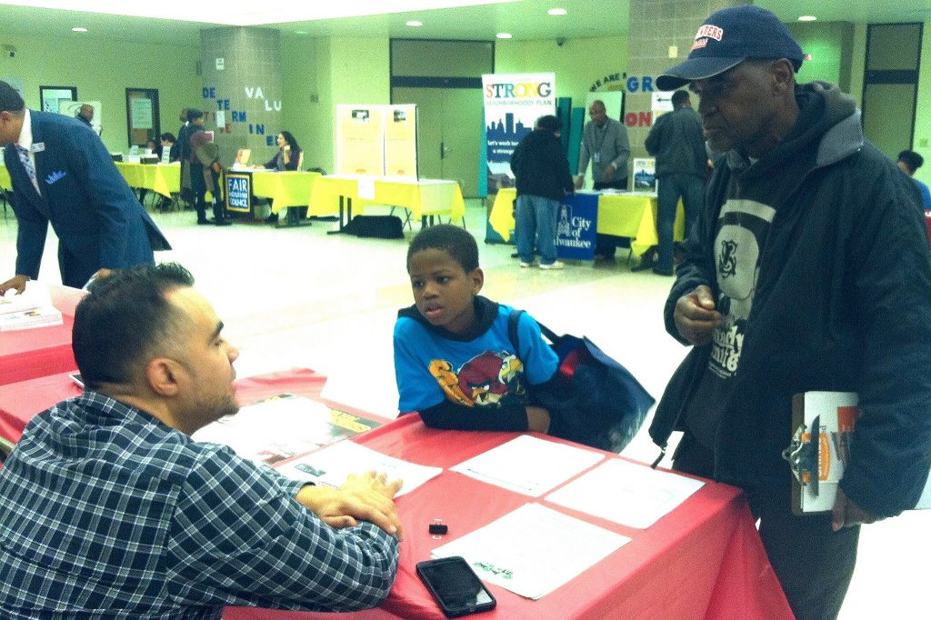 Bert Simmons and his son, Quavon Pollard, get information on housing loans at the housing resource fair. (Photo by Clara Hatcher)