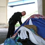 Police officers work to help occupants of homeless encampments