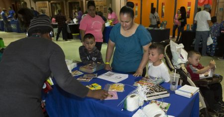 Attendees visit a resource table during the 2018 Celebrando Nuestras Familias event.