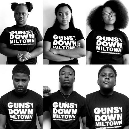 Teens wearing t-shirts emblazoned with Guns Down Miltown logo