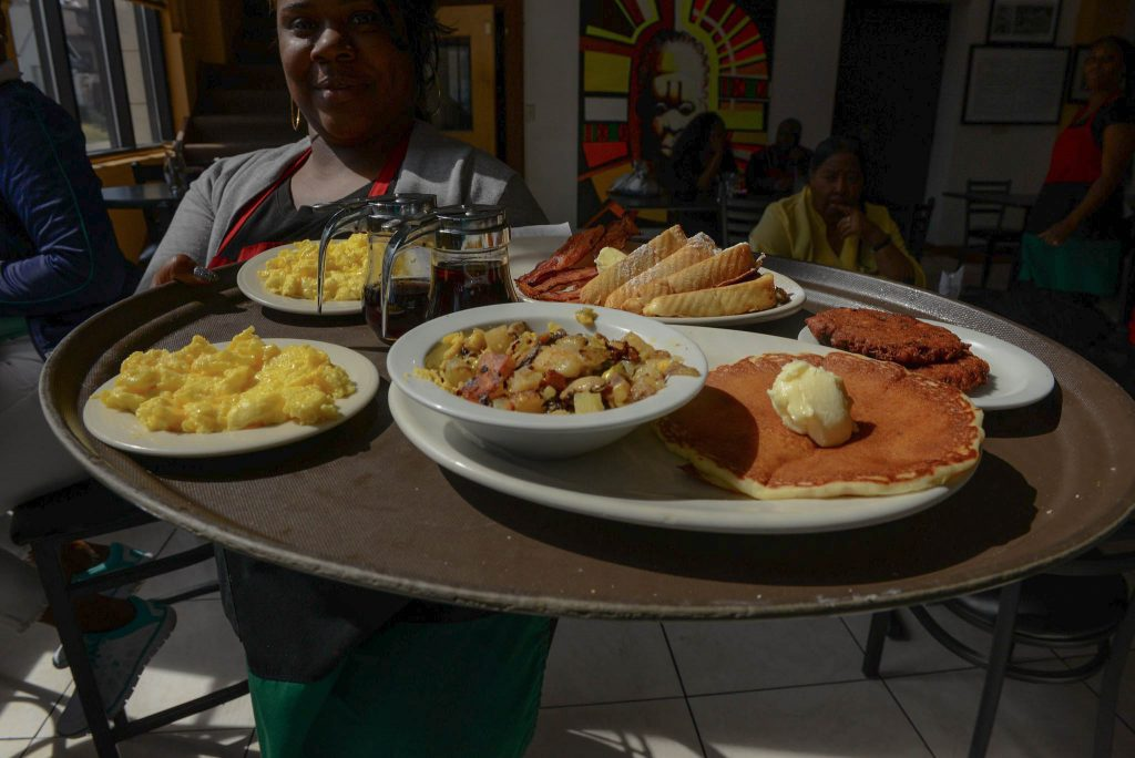 A server at Coffee Makes You Black restaurant with a tray full of breakfast food.