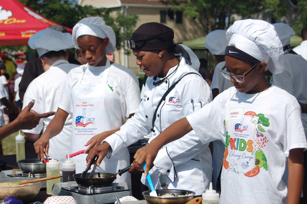 Young cooks at an outdoor cooking event.