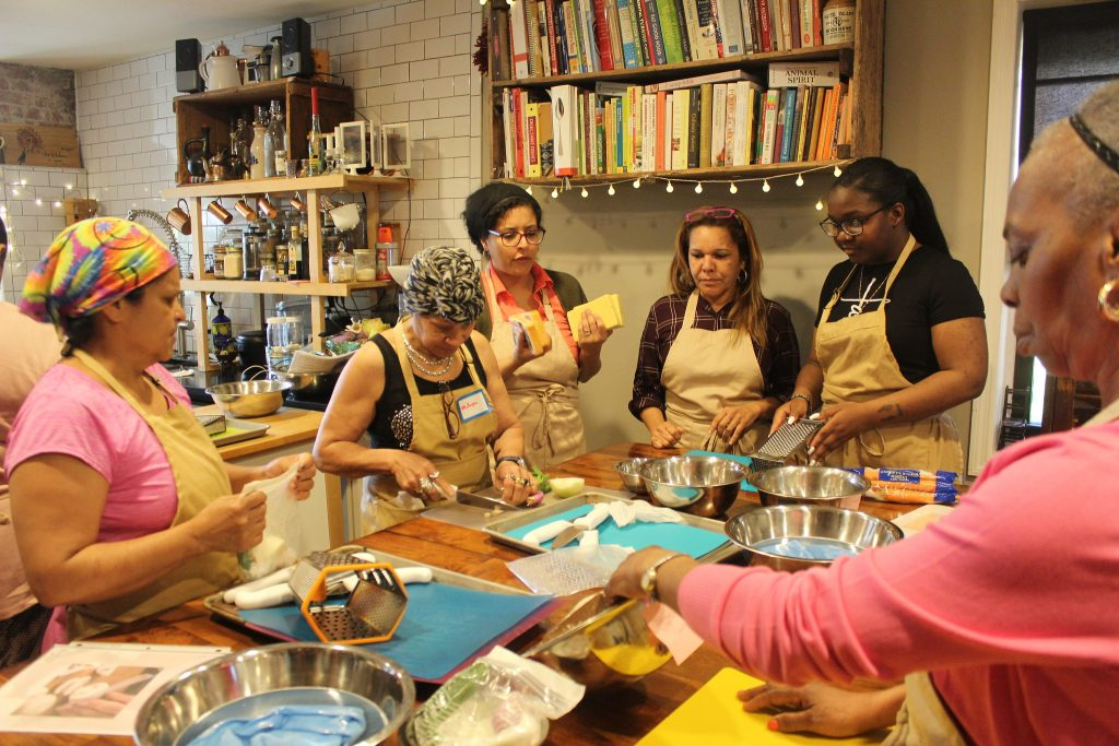 A group of women in a community kitchen cooking class.