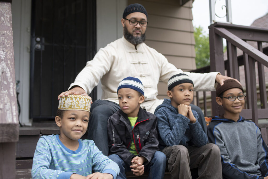 Nazir Al-Mujaahid, and his sons, sitting on the steps in front of their home.